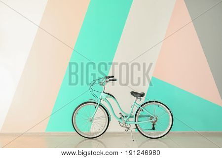 Modern two-wheeled bicycle indoors near color wall
