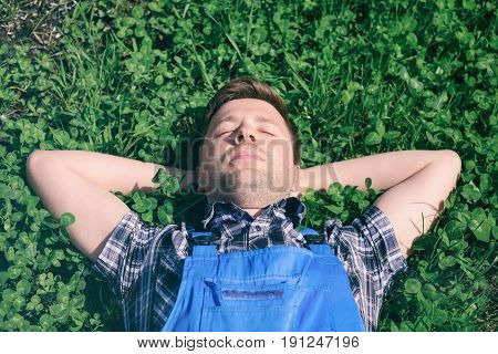 Portrait of a young happy man in working clothes relaxing on the grass. RElax after hard work