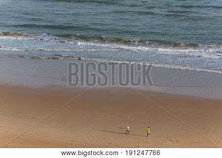 PRAIA DA ROCHA, PORTUGAL - APRIL 22, 2017: People at the beach of Praia da Rocha in Portimao. This beach is a part of tourist region of Algarve.