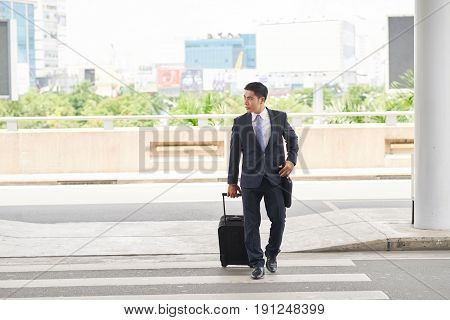 Portrait of modern Asian businessman crossing road with suitcase coming to airport while on business trip