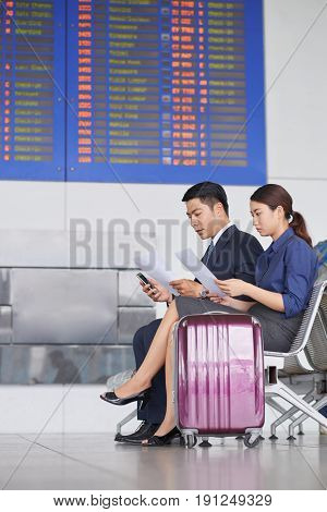 Portrait of two modern Asian  business people, man and woman, waiting for departure on business trip  in airport with big suitcases, sitting against flight information display