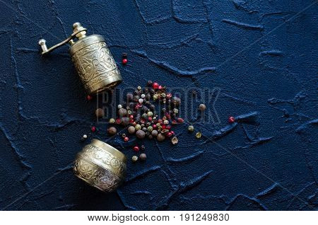 Vintage pepper mill and black red and white peppercorns on dark stone table. Spices concept. Food flat lay. Creative layout with place for text. Copy space. Top view.