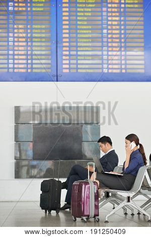 Side view portrait of modern Asian business people, man and woman, waiting for departure on business trip in airport with big suitcases, sitting against flight information display