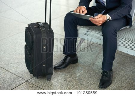 Low section portrait of businessman using digital tablet while waiting in airport with suitcase