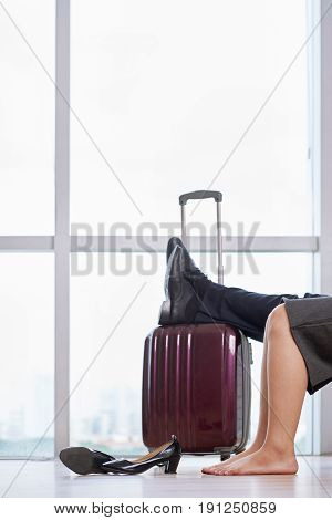 Portrait of relaxed couple in comfortable waiting lounge of airport, taking their shoes off