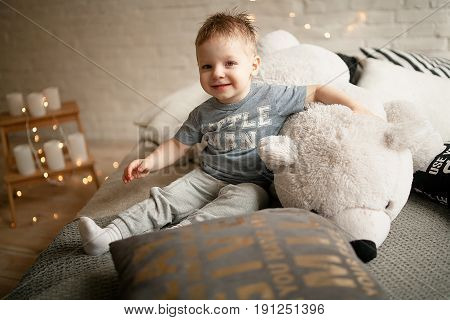 Toddler sits on bed and hugs teddy bear. He smiles.