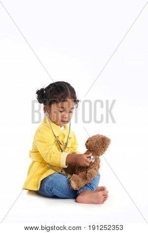 Full length portrait of serious toddler sitting in lotus position and listening to heartbeat of her teddy bear with help of stethoscope, isolated on white background
