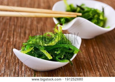 goma wakame or seaweed salad in some white ceramic bowls, on a rustic wooden table
