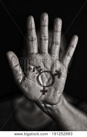closeup of a transgender symbol painted in the palm of the hand of a young caucasian person in black and white