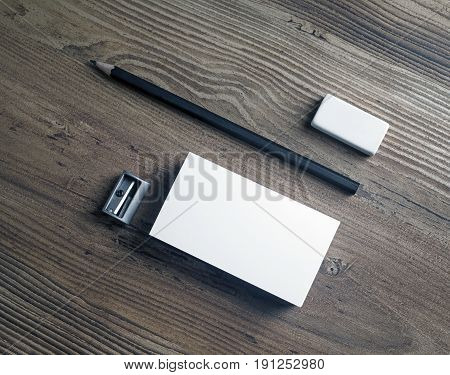 Blank business card pencil eraser and sharpener on wooden background. Mockup for ID. Template for placing your design. Top view.