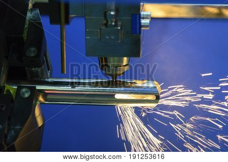 The CNC fiber laser cutting machine cutting the steel pipe with the sparking light.The fire flame from the fiber laser cutting machine.