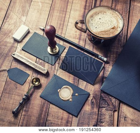 Photo of blank black vintage stationery elements on wood table background. Responsive design mockup. ID template.