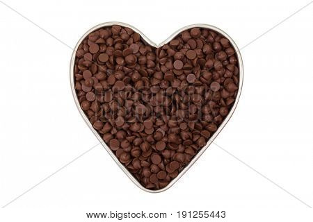 Small chunks of sweetened chocolate chips in heart shaped tin bowl isolated on white background