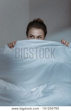 Close-up Portrait Of Young Woman Covering Face With Bedcover In Bed