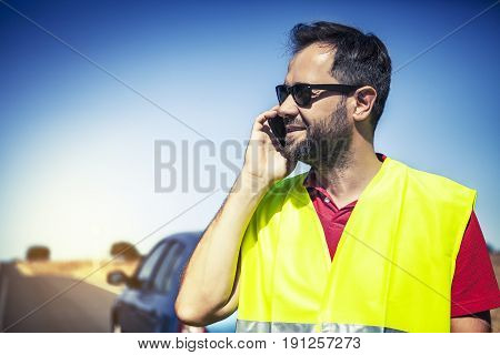 Smiling man in reflective vest talking with insurance company after car breakdown.