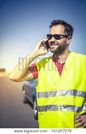 Smiling an talking with car insurance company by phone after a car breakdown