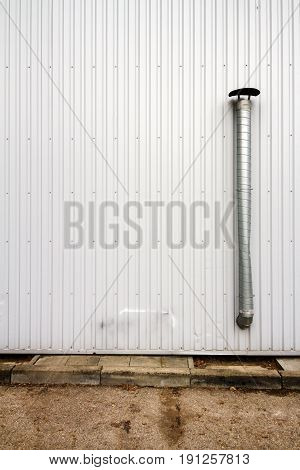 White industrial grooved metal wall with metal chimney