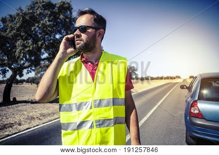 Man talking with car insurance company by phone after a car breakdown