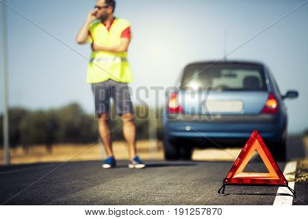 Car breakdown concept. Emergency triangle, man in reflective vest and breakdown car on the road.