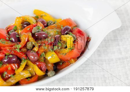 Peppers cooked in pan with oil olives and capers. Typical Italian cuisine ready to eat. White bowl on white background.