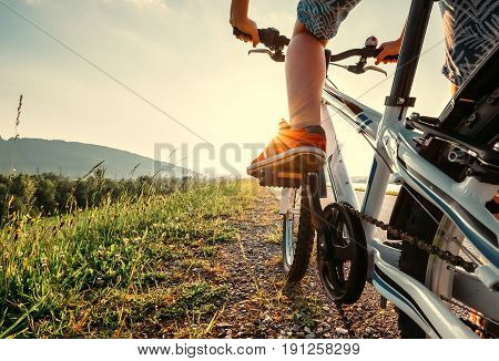 Boy feet in red sneackers on bicycle pedal close up image