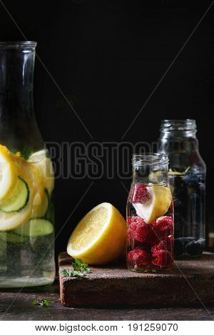 Citrus cucumber berries blueberry and raspberry sassy sassi water for detox in glass bottles on dark black background. Clean eating, healthy lifestyle concept, sunlight