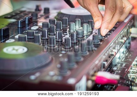 DJ playing music at mixer and mixes the track at the summer beach party