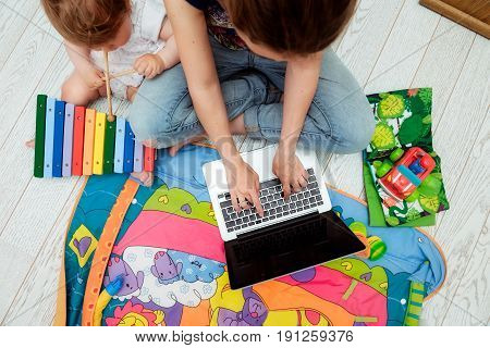 Close Up Photo Of Young Mother Working On Laptop With Her Toddler Child. Freelance Business Concept.