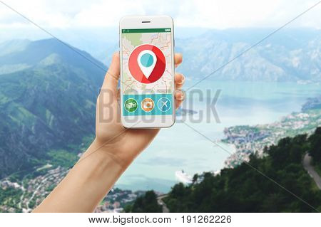 Travel apps concept. Woman using map application in smartphone for planning route and landscape on background