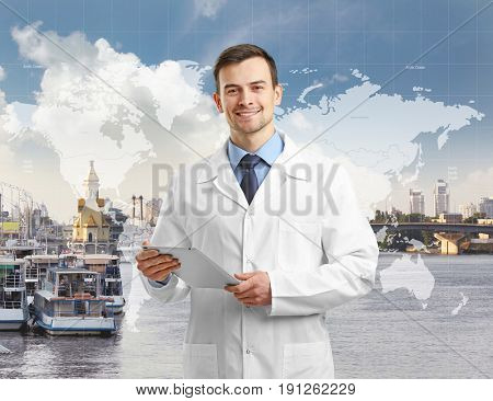 Travel nursing concept. Yong doctor holding tablet on cityscape background