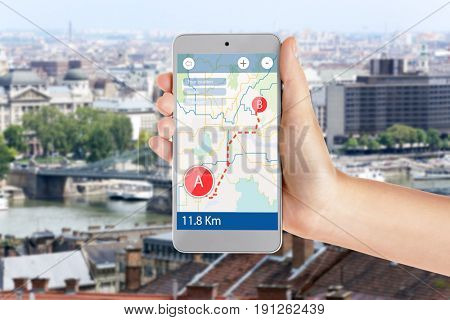 Travel apps concept. Woman using map application in smartphone for planning route and cityscape on background