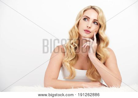 Portrait of beautiful young woman with wavy blond hair looking away pensively against white background, thinking