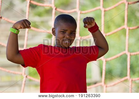 Portrait of boy standing in the boot camp during obstacle course training