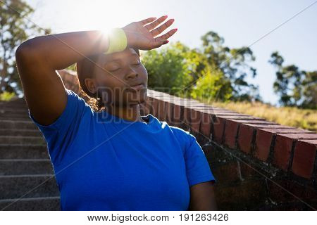 Tired woman standing with hand on forehead in the boot camp on a sunny day
