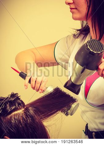 Professional hair styling concept. Hairdresser drying woman dark long hair using hair dryer and brush