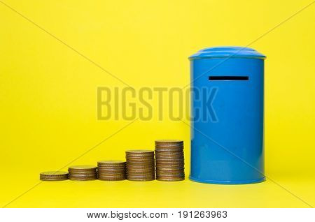 piggy bank or vintage retro blue post box shaped money box with money coin stack growing on yellow background financial business saving money concept selective focus