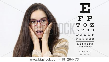 amazement female face with spectacles on eyesight test chart background eye examination ophthalmology concept