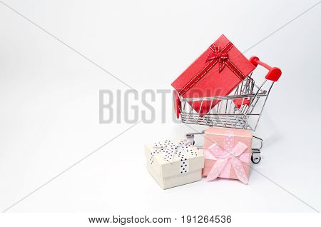 mini supermarket shopping cart with mini colorful gift box on white background holiday sale and online shopping concept selective focus copy space