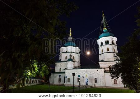 Orthodox white church in Irkutsk at night with moon