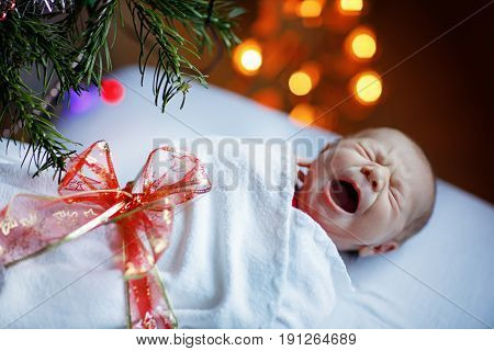 One week old newborn baby wrapped in blanket near Christmas tree with colorful garland lights on background. Closeup of cute child, little baby crying. Family, Xmas, birth, new life