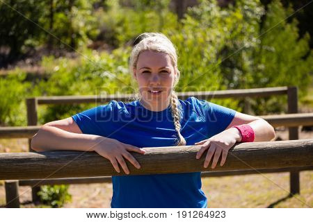 Portrait of fit woman leaning on hurdles during obstacle course training in the boot camp