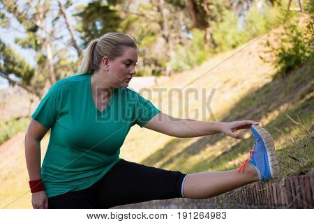 Woman performing stretching exercise during obstacle course training in the boot camp