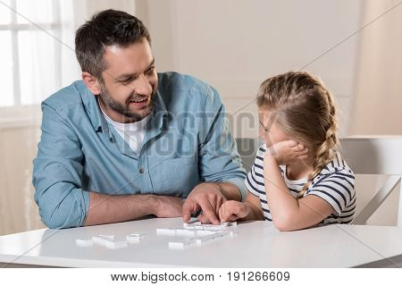 man playing domino with daughter at home