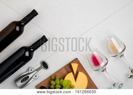 Two glasses of white and red wine, cheese and grapes. Two bottles of wine and a corkscrew. Top view with copy space