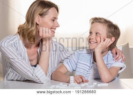 Motherand Son At Table With Domino Pieces