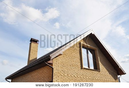 Attic construction outdoors. Roofing Construction with brick chimney and roof gutters system. Mansard roof.