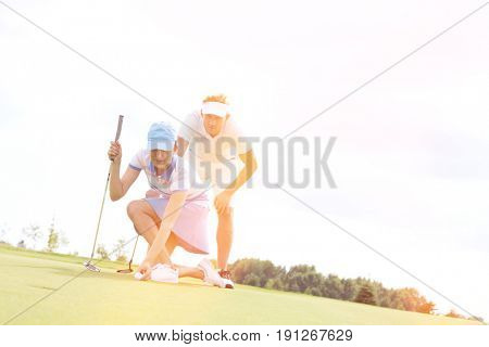 Mid-adult man looking at woman aiming ball on golf course