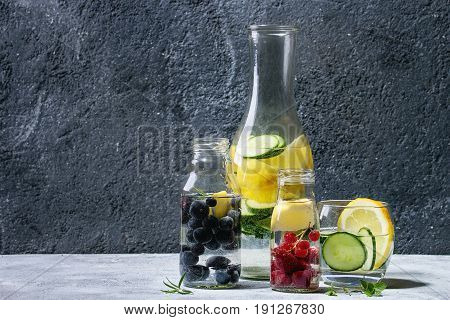 Citrus cucumber berries blueberry and rasberry sassy sassi water for detox in glass bottles on gray texture background. Clean eating, healthy lifestyle concept, sunlight