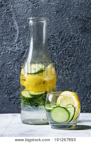 Citrus cucumber sassy sassi water for detox in glass bottle on gray texture background. Clean eating, healthy lifestyle concept, sunlight