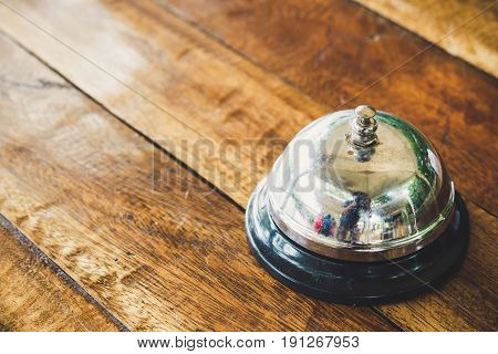 Silver bell service isolated the wooden table.
